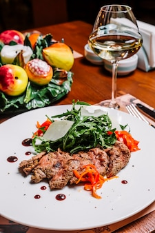 Lamb steak served with rocket parmesan and red chili peppers