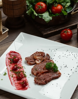 Lamb steak slices with cornelian cherry and sauce on white square plate