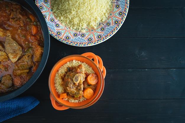Баранина с кус-кусом на черной деревянной поверхности. скопируйте пространство. арабская еда. вид сверху.