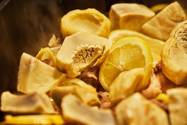 레몬, 아티초크, 고수 줄기를 곁들인 양고기를 가마솥에서 약한 불로 튀깁니다.