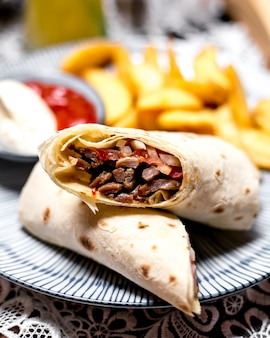 Lamb wrap served with potato fries ketchup and mayonnaise