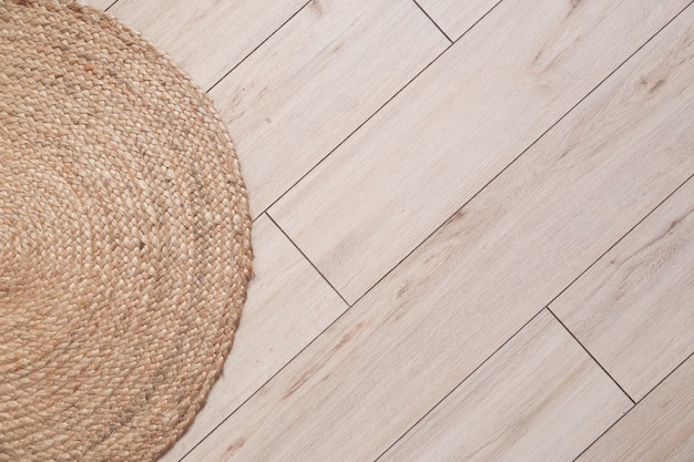 모따기 및 고리 버들 카펫이있는 라미네이트 바닥 패널. 상위 뷰, 배경.