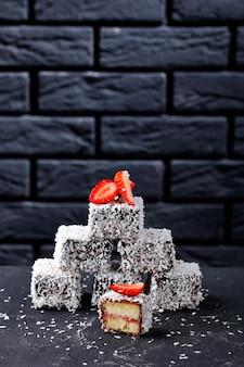 Мини-пирожные с ванильным бисквитом lamingtons с прослойкой клубничного джема внутри, покрытые шоколадом и кокосом сверху на темном бетонном столе
