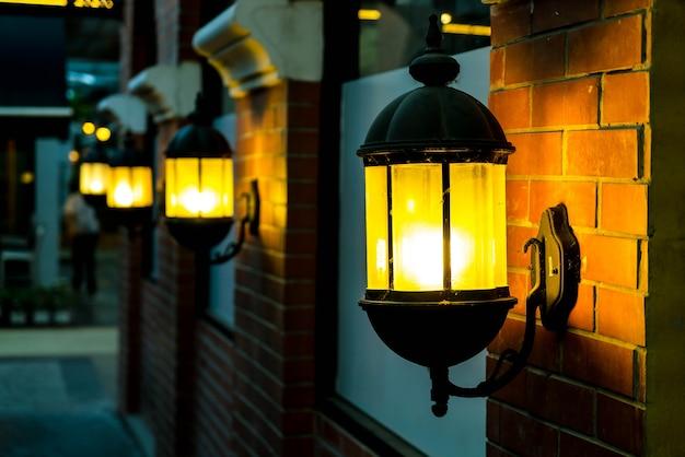夜に赤いレンガの壁にランプ。