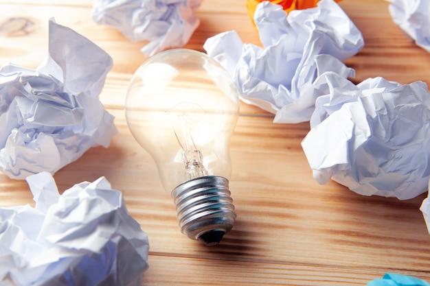 Лампа и скомканные бумаги на столе. концептуальная идея