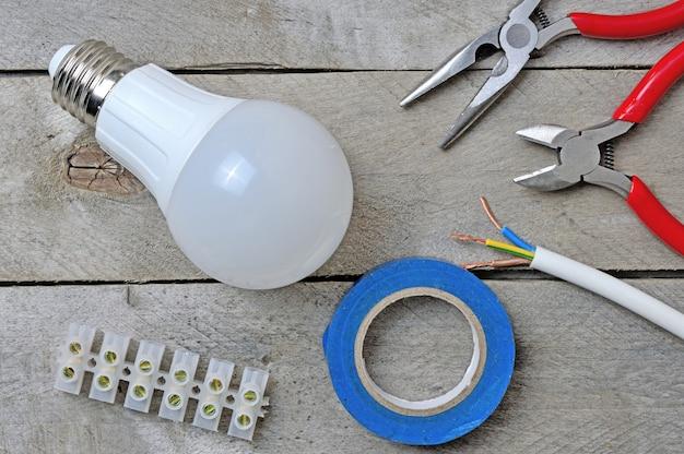 木製の背景にランプと電動工具。上面図。