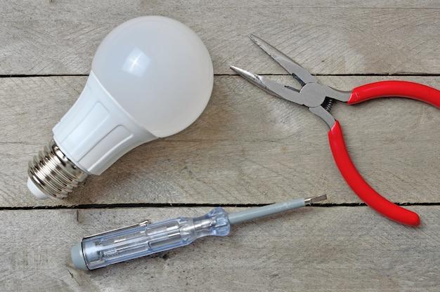 Лампа и электрический инструмент на деревянном столе. вид сверху.