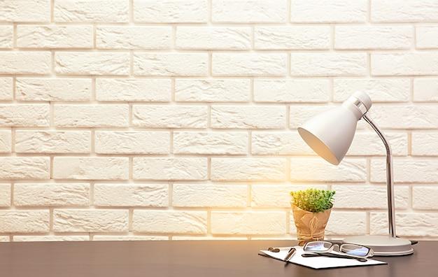 ランプと壁の背景の机の上の植物