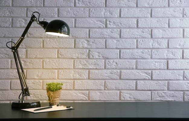 壁の背景の机の上のランプと植物