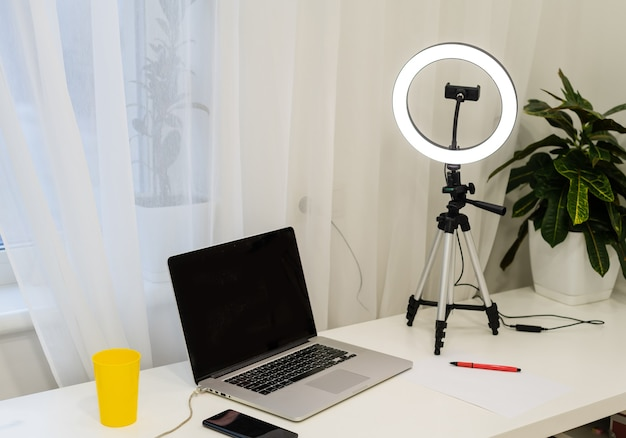 노트북 뒤에서 온라인 인터뷰를 위한 테이블 위의 램프와 삼각대
