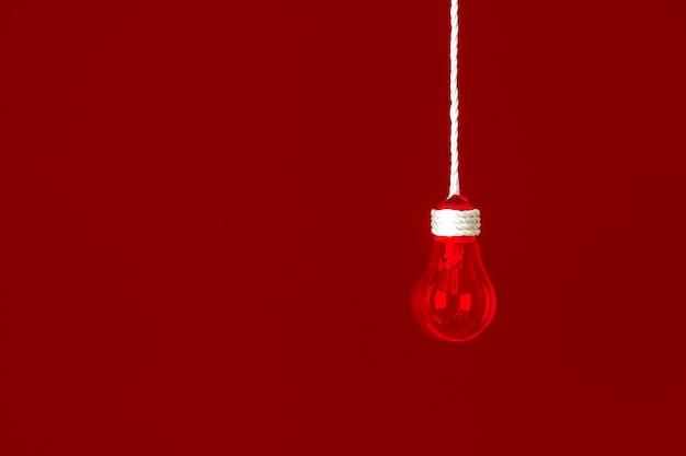 Лампочка лампы висит на веревке. красный фон. концепция новой идеи.