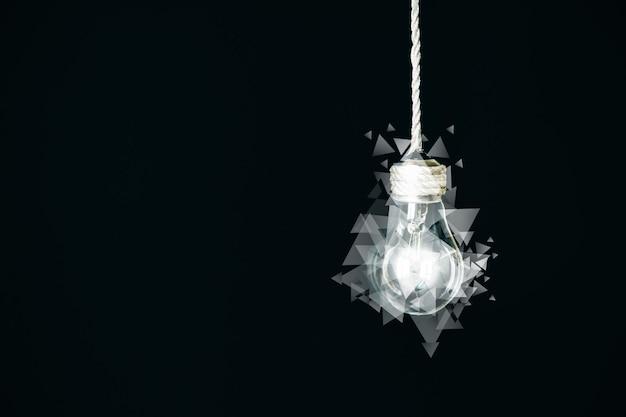 Колба лампы с треугольниками, висящая на веревке. концепция новой идеи. художественная идея. изолированные на черном фоне.