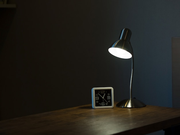 Lamp and clock in the dark room with light and shadow concept