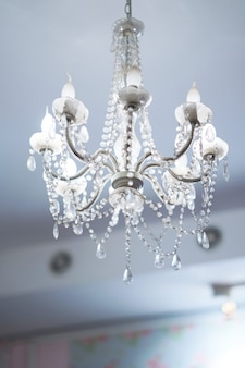Lamp hangs on ceiling by chandelier style