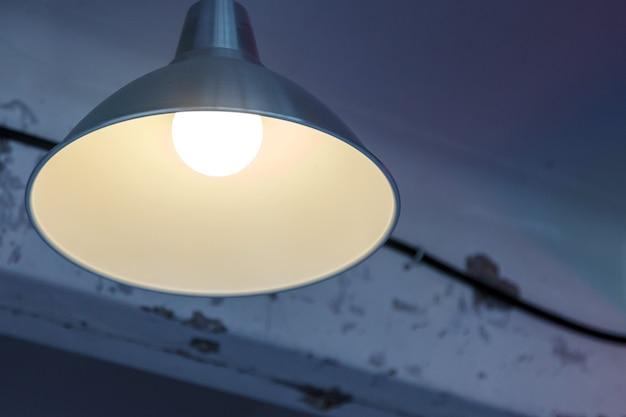 古い織り目加工の天井に日陰のランプ。ぼろぼろの背景の照明装置