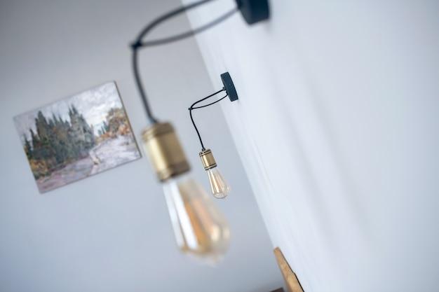 ランプ、ミニマリズム。日光の下で自宅の部屋の白い壁に掛かっている2つのミニマリストランプ