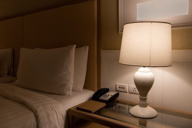 Lamp on a night table next to classic bed.
