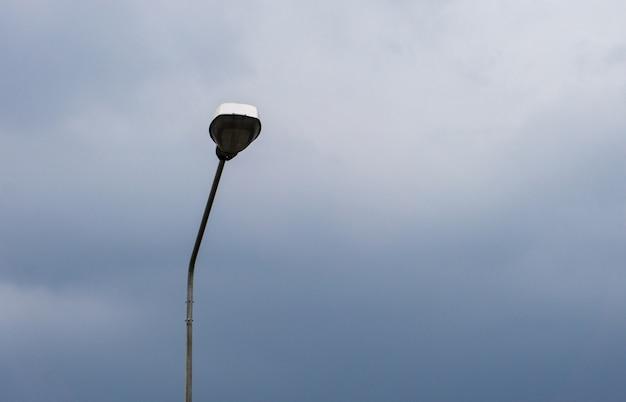 通りの雲の空のランプ。トワイライトタイム、ランプ節約エネルギー、閉鎖ライト