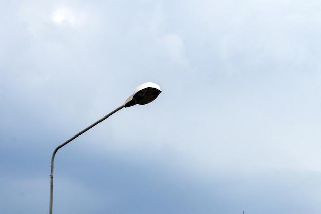 通りの雲の空のランプ。トワイライトタイム、ランプはエネルギーを節約します。