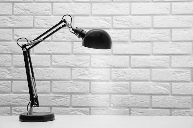 白いレンガの壁の背景に机の上のランプ