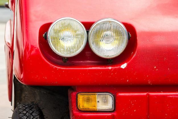 赤いビンテージ車の前のランプ部品