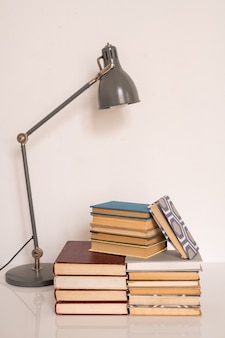 Lamp over stacks of books and manuals on table or workplace of student of college or school against white wall in studio