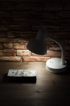 A lamp standing on a wooden table near a brick wall illuminates a bundle of dollars.