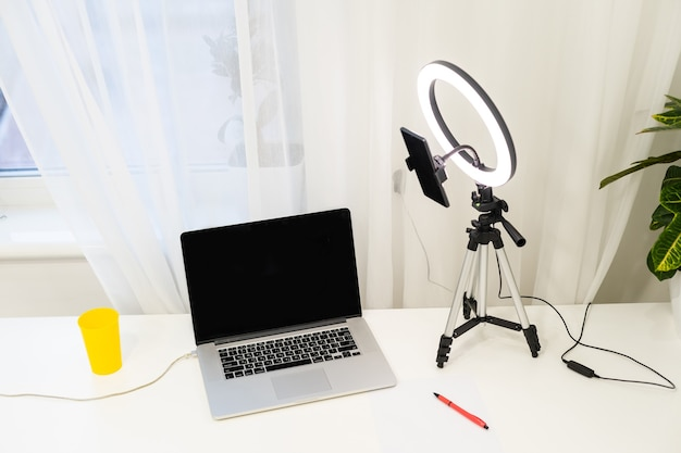 Lamp and tripod on the table for online interviews behind a laptop