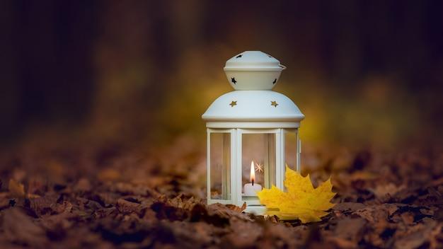 乾燥した秋の葉の上に夜のキャンドルとランプ。