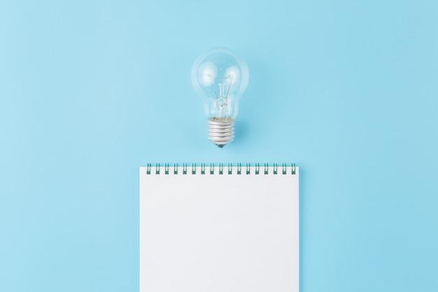 Лампа с блокнотом на синем фоне