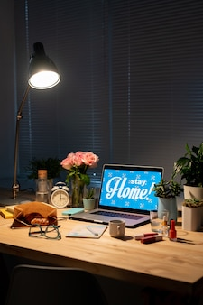 Lamp over wooden table with flowers, domestic plants, laptop, snack, drink, alarm clock, cosmetic products, eyeglasses and copybook in dark room