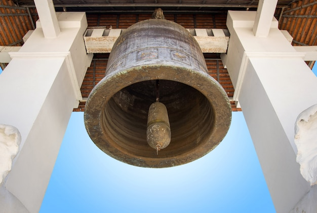 Старый церковный колокол с голубым небом в виске lamphun, таиланда