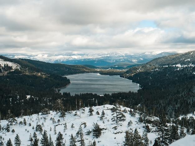 Terra coperta di neve che si affaccia sul lago donner a truckee, california, sotto un cielo nuvoloso