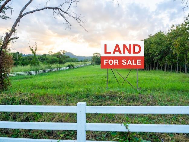 흰색 나무 울타리로 둘러싸인 빈 땅에 판매 사인에 대 한 토지