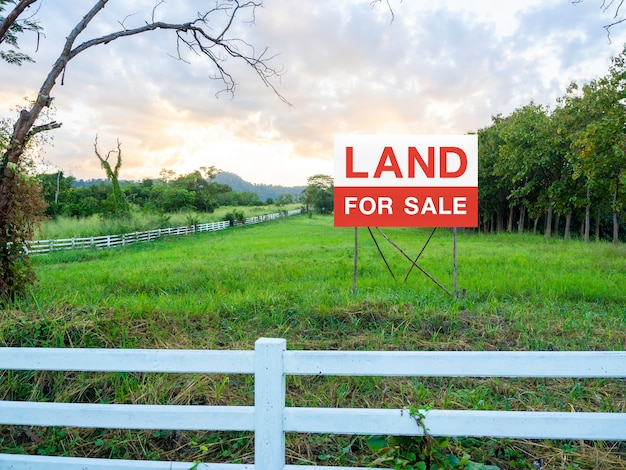 Land for sale sign on empty land, surrounded with white wooden fence