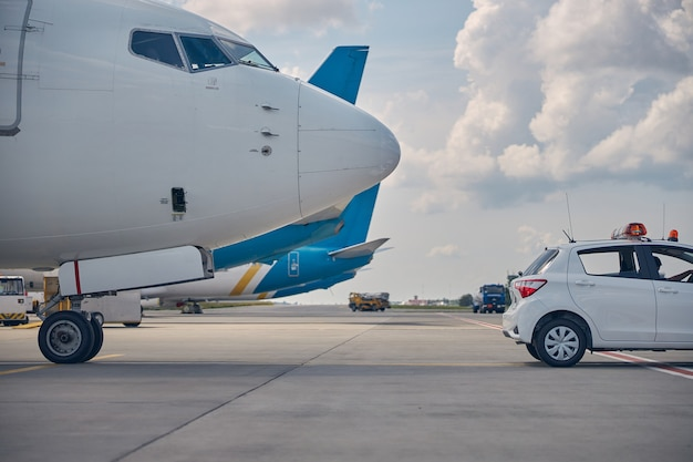 Landed large civil aircraft taxing after a follow-me car to the parking spot at the aerodrome
