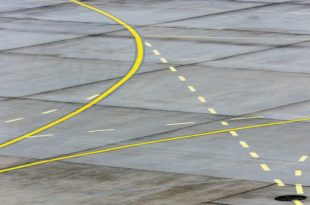 Landing light directional sign markings on the tarmac of runway at a commercial airport.