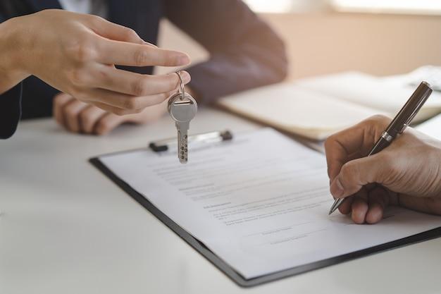 임대 계약서에 서명 한 후 세입자에게 집 열쇠를주는 집주인.