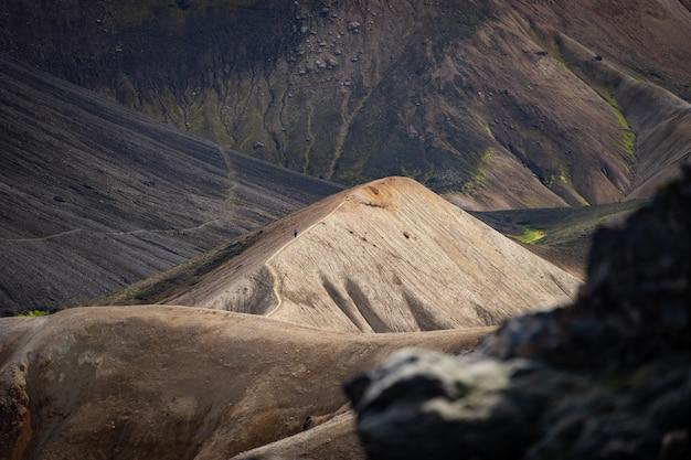 Ландманналаугар красочный холм на черном ясене в туристической тропе лаугавегур. исландия. сочетание слоев разноцветных горных пород, минералов.