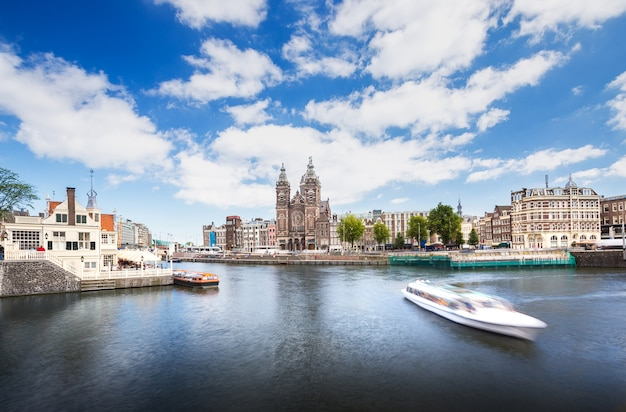 Landmark along canal with cruise, tram, bus transportation amsterdam, netherlands
