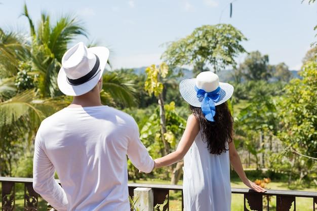 Вид сзади молодая пара, держась за руки, ходить на летнюю террасу или балкон, чтобы посмотреть на тропических landsc