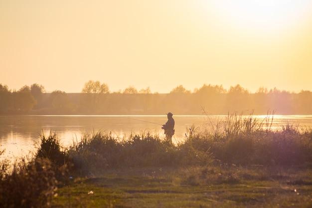 Пейзаж - река на закате и рыбак на берегу реки