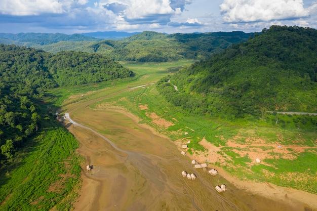 青い空と地面と山の緑の自然林に竹のいかだで空撮渓谷を風景します。