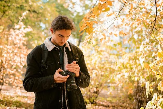 Фотограф пейзаж и природа смотрит на свои снимки на камеру