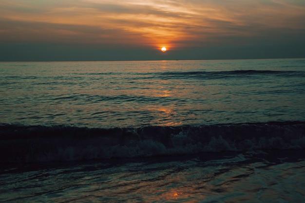風景と夕日の海の光はオレンジレッドを反射します。