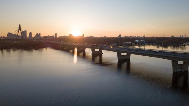 ウクライナ、キエフのオボロン地区、ドニエプル川を渡るノースブリッジの吊り下げのある風景と夕日。ドローンからの写真