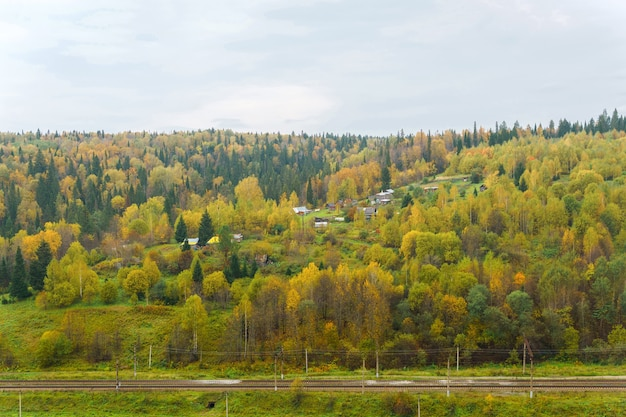 樹木が茂った丘と鉄道の間に村がある秋の川の谷の風景