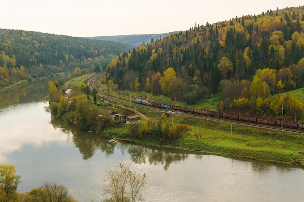 Landscape autumn river valley with a village between wooded hills and the railroad along which the freight train goes