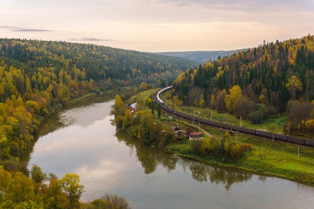 Landscape autumn river valley with a village between wooded hills and the railroad along which two freight trains goes