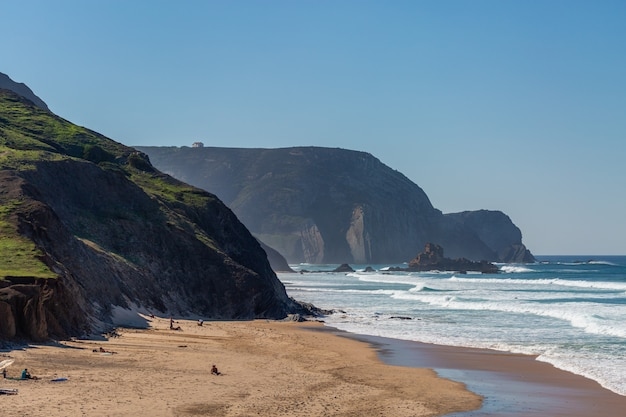 Landscape of a beach surrounded by sea and mountains with people around it in portugal, algarve